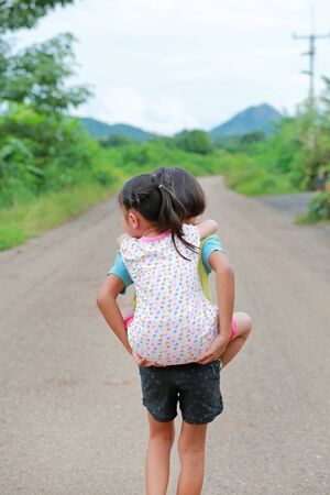 Young asian girl and his sister ride back and walking on road. 版權商用圖片