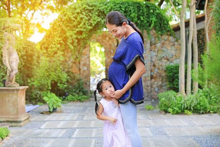 Beautiful little girl hugging a pregnant and kissing mothers belly in the garden.