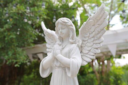Rzeźba anioła w ogrodzie.