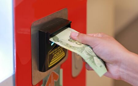 Hand inserting banknote into vending machine.