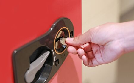 Hand inserting coin into vending machine. 写真素材