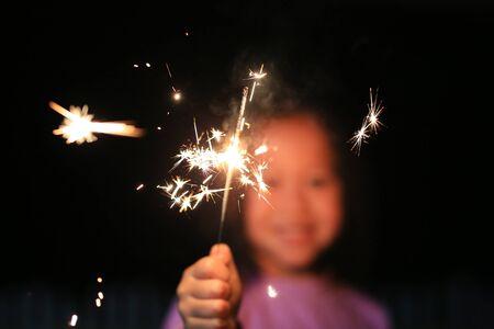 Ciérrese encima de la pequeña muchacha asiática que sostiene las bengalas del fuego. Foto de archivo