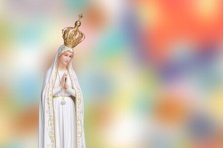 Standbeeld Maagd Maria Fatima van de katholieke kerk op kleurrijke achtergrond wazig. Stockfoto