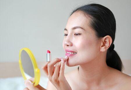 Portrait of beautiful woman applying lipstick. Beauty Concept.