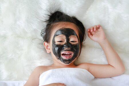 Kid girl in black peeling face mask, beauty concept.