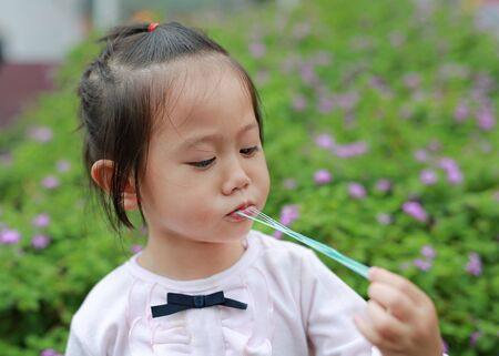 Cute little girl enjoy eating bubble gum.