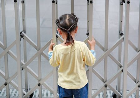 Back view of child girl holding steel fence.