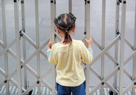Vista posterior de la muchacha del niño que sostiene la cerca de acero.