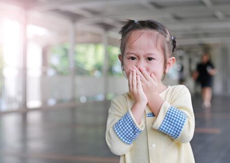 Little asian girl covering her mouth with her hands. Child sneezing.