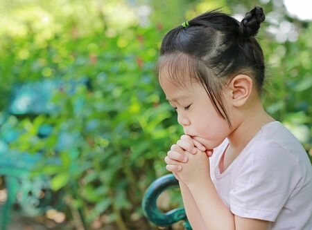 Little child girl praying in the garden 스톡 콘텐츠