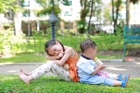Happy Family. Little Asian sister and her younger brother sit back and lean back together in the green garden. Child girl cuddle teddy bear doll and boy Suck milk from bottle.
