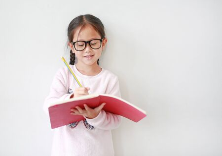 Asian Schoolgirl wearing eyeglasses holding and writes in a notebook with pencil on white background. 写真素材