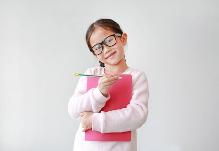 Asian schoolgirl wearing eyeglass hug a book and holding pencil in hand against white background. Portraits of child girl looking straight at camera.