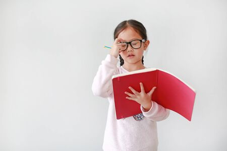 Portrait of little Asian Schoolgirl wearing eyeglasses and holding notebook with pencil on white background.