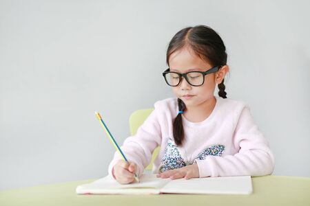 Portraits of little Asian child girl wearing eyeglasses and write in a book or notebook with pencil sitting on kid chair and table against white background. Stock fotó