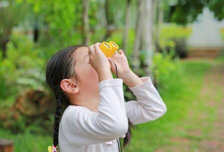 Kid girl kid looking ahead with binoculars in nature fields. Explore and adventure concept.