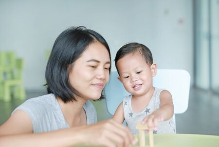 Mom and little baby boy playing wood blocks tower game for Brain and Physical development skill in a classroom. Focus at children face. Child learning and mental skills concept. Stockfoto
