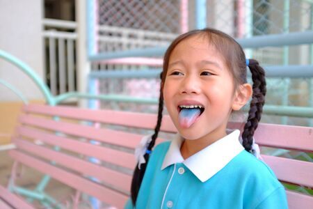 Funny face little Asian child girl smile and poking out blue colored tongue. Food coloring in children sweets. Foto de archivo