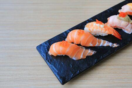 Sushi seafood set served on black stone plate on wood table. Japanese cuisine. Stock Photo - 129398940