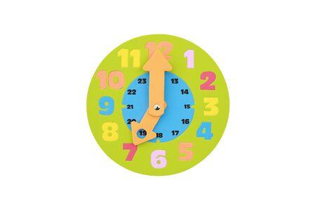 Reloj de juguete redondo de las 7 en punto aislado sobre fondo blanco. Foto de archivo