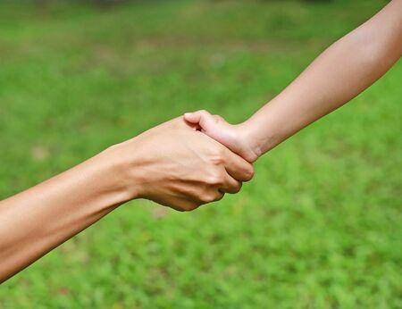 Nahaufnahme von Mutter und Kind, die sich an den Händen halten Standard-Bild