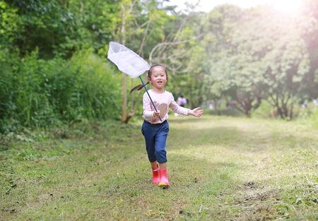 Adorable little asian girl wear straw hat playing in a field with insect net in summer