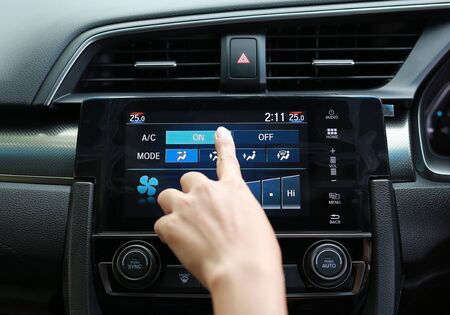 Finger pressing the button on the air conditioner in the modern car dashboard Фото со стока