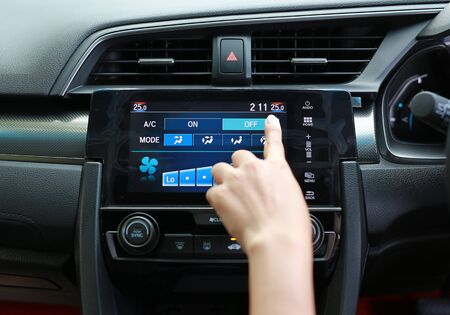 Finger pressing the button off the air conditioner in the modern car dashboard