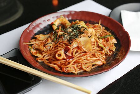 Japanese yakisoba noodles in brown ceramic plate on the black table Stockfoto