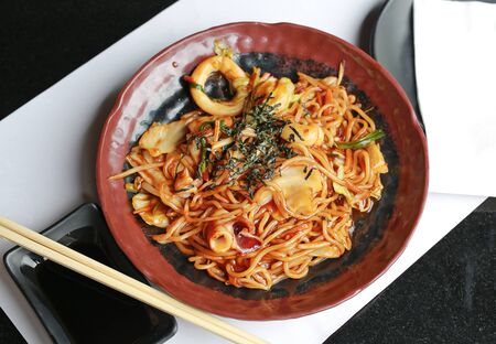 Japanese yakisoba noodles in white plate on wood table