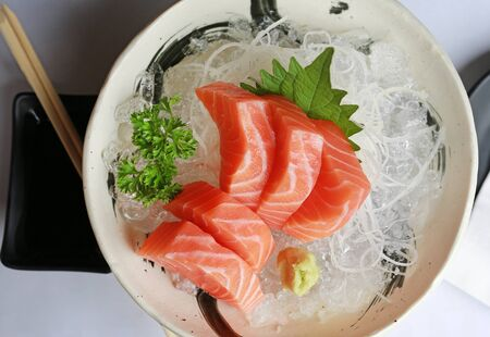 Salmon raw slice or salmon sashimi in Japanese style fresh serve on ice. Top view.