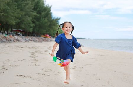 Happy kid girl running on the beach with holding a pinwheel in her hand Banco de Imagens