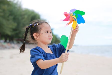 Child girl with a spinning pinwheel on the beach