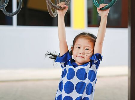 Cute asian girl playing on gymnastic ring with looking at camera.