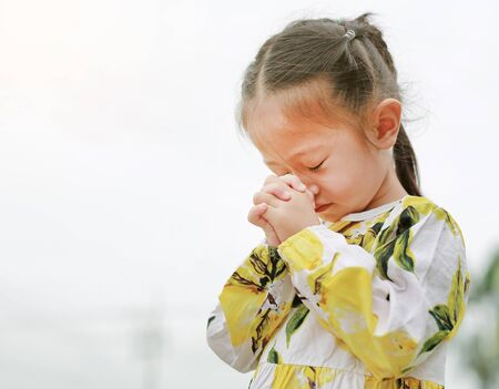 Little asian girl stance praying in the garden at the morning. Little kid girl hand praying, Hands folded in prayer concept for faith, Spirituality and religion. 스톡 콘텐츠