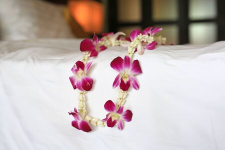 Welcome orchids garland place on the bed of luxury hotel in thailand. Stock fotó
