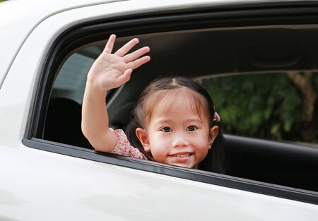 Asian little girl in car smiling and looking camera sitting on a backseat of a car waving goodbye. Transportation concept. Foto de archivo - 129523524