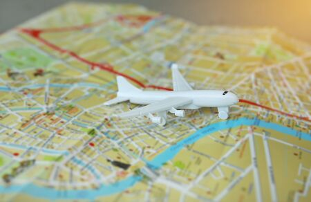 Mini airplane model on a map with rays of sunlight, world travel concept. Foto de archivo - 129523731