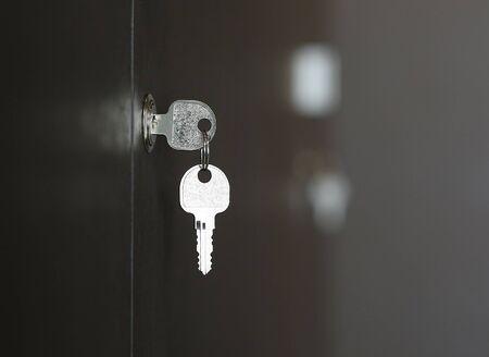 Key in keyhole on wooden cabinet, key in lock. Stock Photo