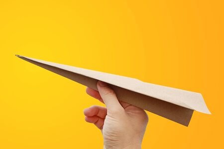 Brown aircraft rocket paper in hand fold to success isolated on yellow-orange background, Concept for business and travel plant. Stock Photo