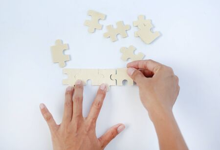 Closeup hands connecting jigsaw puzzle on white background