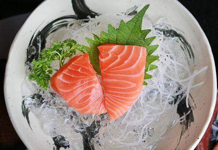 Close-up Salmon raw slice or salmon sashimi in Japanese style fresh serve on ice.