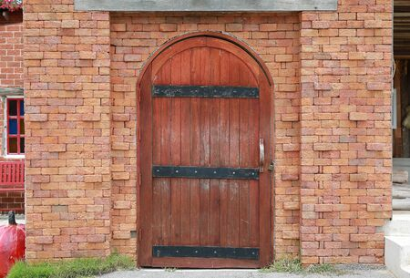 Arched wooden door with key locked in red brick wall