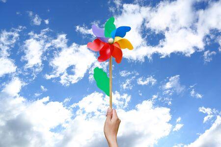 Hand holding pinwheel against sky Stock fotó