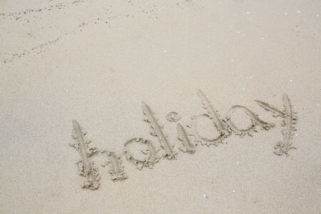 Holiday written in the sand on the beach