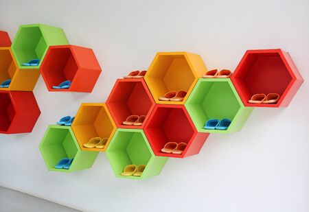 Colorful Modern Shoe Rack on the white wall. Stock Photo