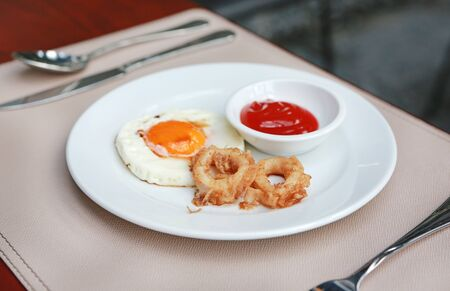 Fried calamari rings and fried egg with tomato sauce on plate