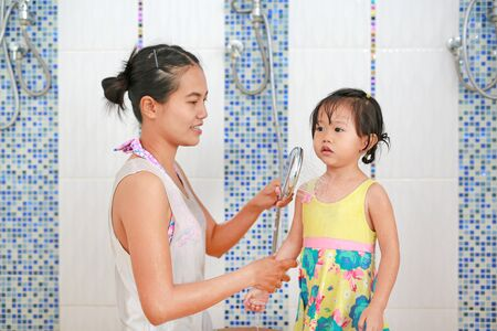 Mother pours water from shower for child to warm up body before swim