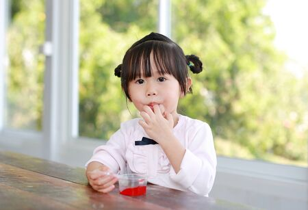 Child girl licking her fingers while eating.