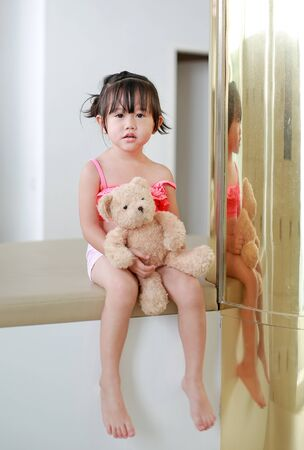 Portrait of asian child girl in swimming suit lying on sofa with reflection pole